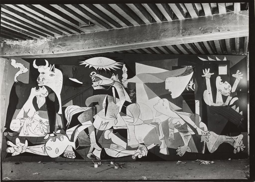 "A photo by Dora Maar of ""Guernica"" as a work in progress in Picasso's studio on Rue des Grands Augustins in Paris. © Succession Picasso © ADAGP, Paris. Photo: © RMN-Grand Palais (Musée National Picasso-Paris)/Mathieu Rabeau"