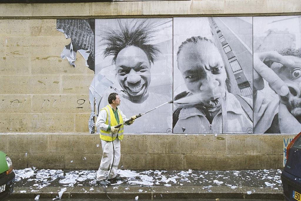 """28 Millimètres, Portrait d'une Génération, Kärcher Série,"" (2006). JR's images being blasted off a wall in Paris. © JR-ART.NET"