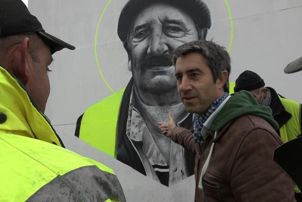 François Ruffin points to a Christ-like portrait of a Gilet Jaune, a retiree who has difficulty making ends meet, in the documentary J'Veux du Soleil.