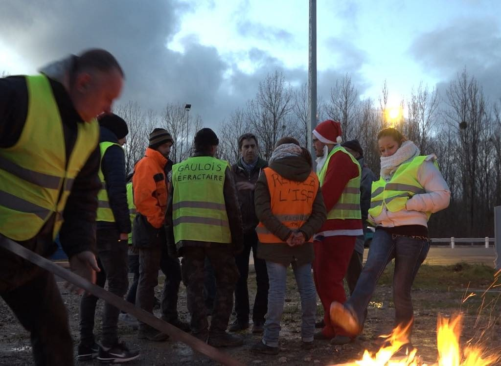 Gilets Jaunes trying to keep warm on the roundabout in December.
