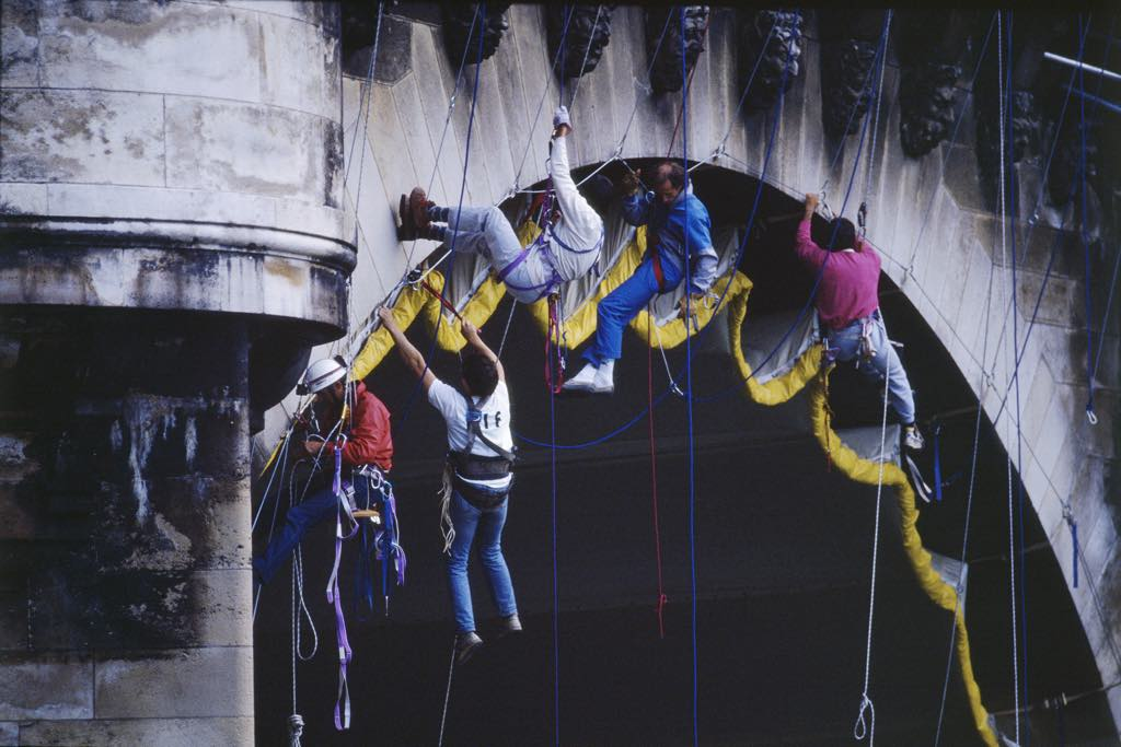Climbers attach the fabric hoisted under one of the arches and adjust the tension of the straps sewn onto the fabric, making it hug the lines of the vault [September 16-22, 1985]. © Christo 1985 Photo © Wolfgang Volz